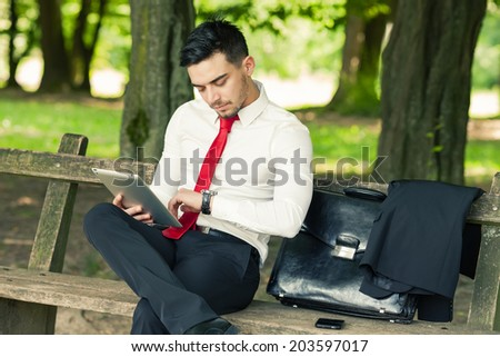 Young and successful business man sitting on the park bench holding a tablet and checking time - stock photo