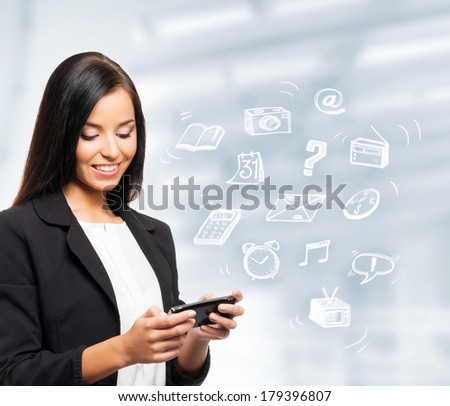 Young and successful business woman with a mobile phone and many drawing icons - stock photo