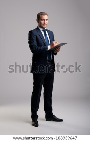 Young and successful businessman holding a clipboard and signing a documen - stock photo