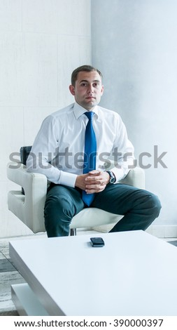 Young and successful businessman is sitting in the chair and waitng a call - stock photo