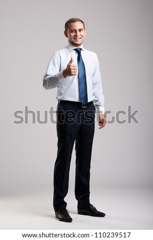 Young and successful businessman showing thumbs up - stock photo