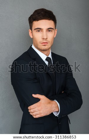 Young and successful. Confident young businessman keeping arms crossed and looking at camera while standing against grey background - stock photo