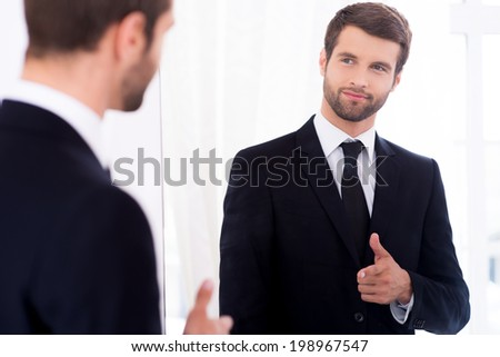 Young and successful. Handsome young man in full suit pointing himself and smiling while standing against mirror - stock photo
