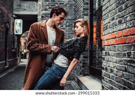 Young and trendy man and woman in passion emotions of the street with brick walls. Fashion style - stock photo