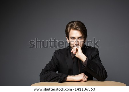Young and very confident businessman sitting on a desk and looking directly at the camera - stock photo