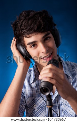 Young and very handsome boy singing, on blue background - stock photo