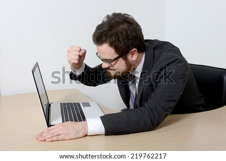 Young angry businessman with laptop   - stock photo