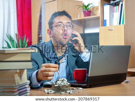 Young angry businessman working on his laptop at home  - stock photo