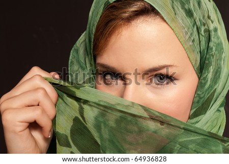 Young arab woman with veil showing her eyes on dark gray background - stock photo