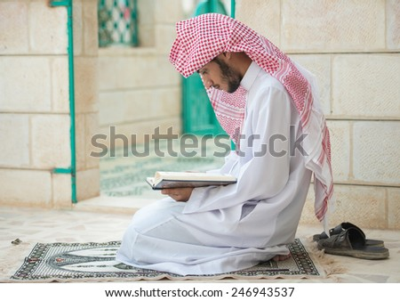 Young Arabic Muslim man reading Koran and praying - stock photo