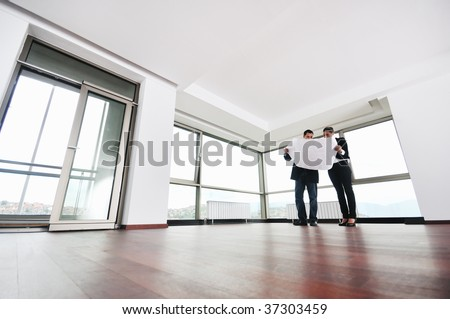 young architect group in big bright modern new apartment looking blueprints and building plans - stock photo