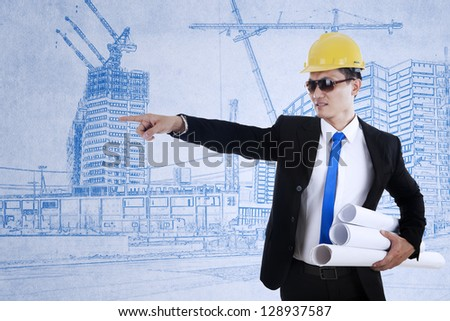 Young architect is pointing at something while holding blueprints - stock photo