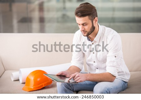 Young architect is using tablet while siting on the couch. - stock photo