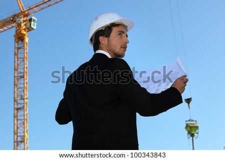 Young architect with a crane in the background - stock photo