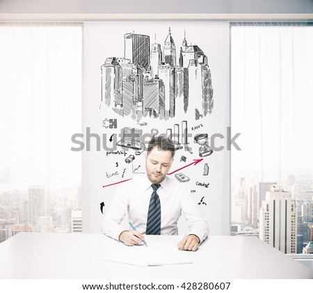 Young architect working in office with construction sketch on wall - stock photo