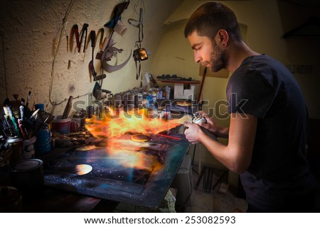 Young artist finishing his artwork with spray paint and fire  - stock photo