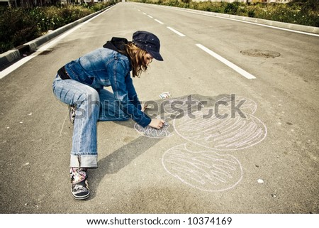 Young artist painting on the street - stock photo