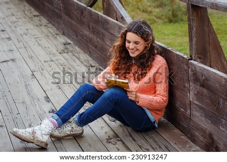 Young artist with sketch in note at autumn landscape - stock photo