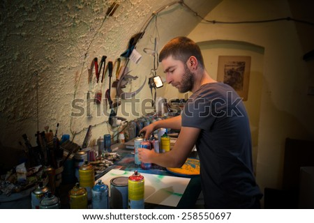 Young artist working in his studio creating artwork using spray paint. - stock photo