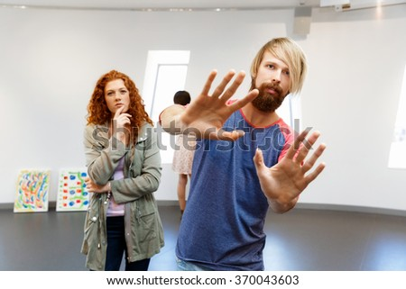 Young artists in gallery hanging painting on walls - stock photo