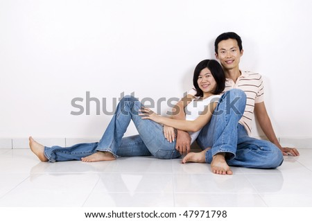Young Asian adult couple sitting together on tiles floor in home smiling. - stock photo