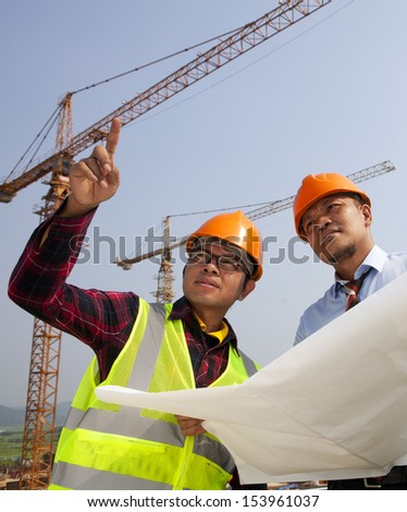 Young asian architects discussion at blueprint in front of construction site,vertical image - stock photo