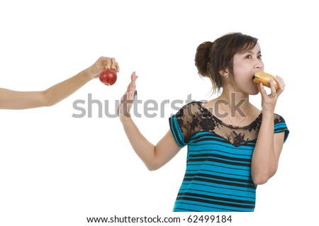 young asian beauty refusing an apple preferring a hamburger, isolated on white background - stock photo