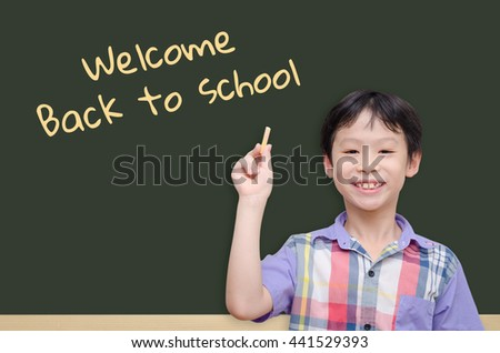 """Young asian boy holding chalk with text """"welcome back to school"""" - stock photo"""
