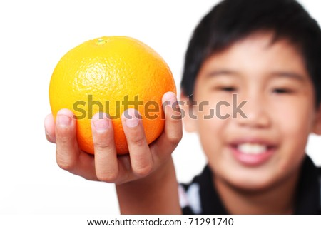 Young asian boy holding/showing a piece of orange fruit. White background. - stock photo
