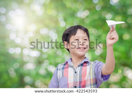 Young Asian  boy playing paper airplane in park - stock photo