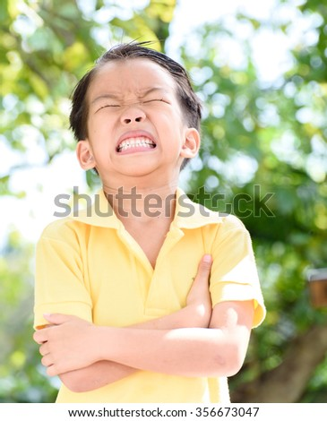Young Asian boy sad and crying in the garden in summer with tree and bokeh. - stock photo