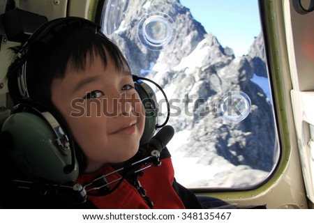 Young asian boy smiling on a helicopter trip in Milford Sound, New Zealand - stock photo