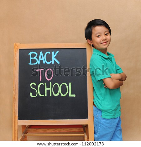 Young Asian boy standing next to a blackboard with Back To School inscription - stock photo