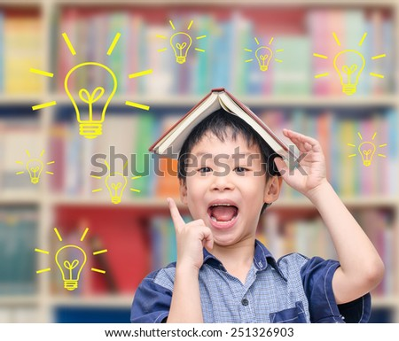 Young Asian boy thinking with light  bulbs in library - stock photo