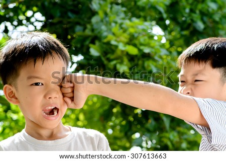 Young asian boy was hit by his brother in front of green bokeh background from tree leaf - stock photo