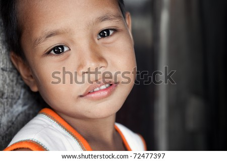 Young Asian boy with soft smile living in poverty stricken area - portrait against wall. Manila, Philippines. - stock photo