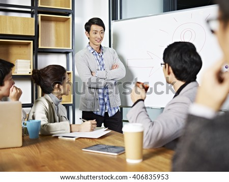 young asian business executive facilitating a discussion or brainstorm session in meeting room. - stock photo