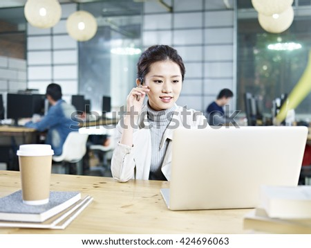 young asian business executive sitting at desk in office working using laptop computer. - stock photo