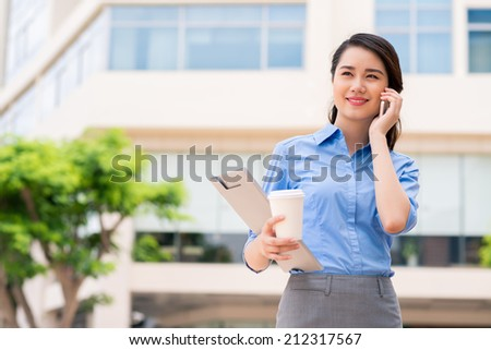 Young Asian business lady talking on the phone outdoors - stock photo