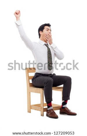 Young Asian business man stretching on the chair isolated on white background. - stock photo