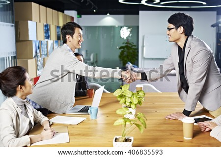 young asian business people shaking hands smiling before meeting or negotiation - stock photo