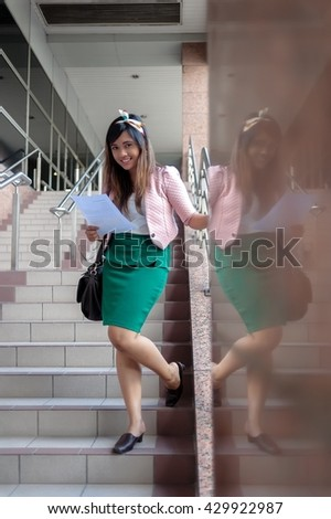 Young Asian business woman smiling, reading a letter, walking at an outdoor office environment - stock photo