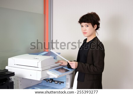 Young Asian business woman using a copy machine. - stock photo