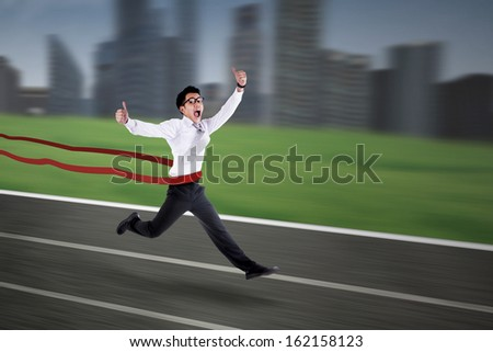 Young asian businessman crossing the finish line with cityscape background - stock photo