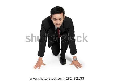 Young Asian businessman in steady position to run toward camera, isolated on white background - stock photo