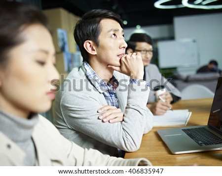 young asian businessman looking up and thinking during meeting in office, hand on chin. - stock photo
