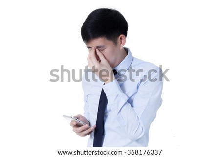 Young Asian businessman rubbing his tired eyes from long hours of works using smart phone - stock photo