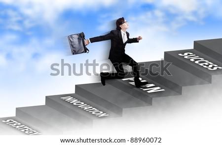 Young Asian businessman running carrying a laptop bag - stock photo