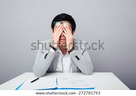 Young asian businessman sitting at the table and rubbing his eyes over gray background - stock photo