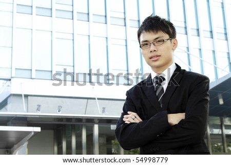Young Asian businessman standing with arms crossed - stock photo